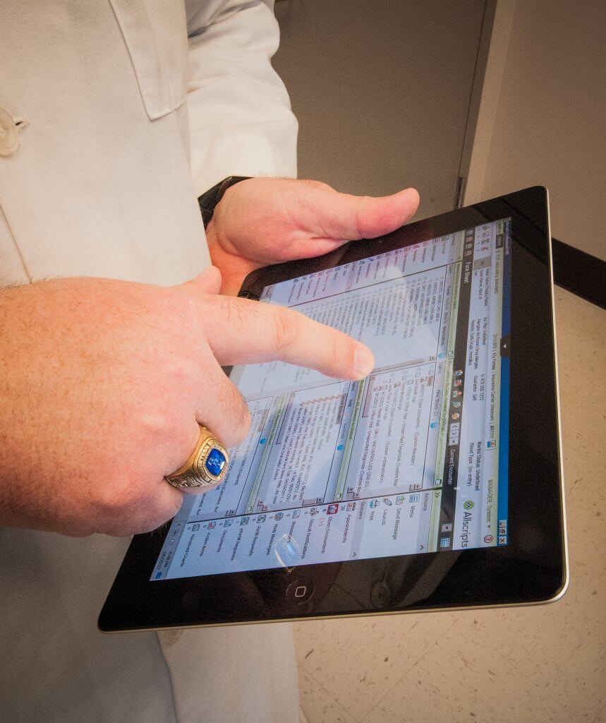 Image of a physician using an electronic charting system on an iPad