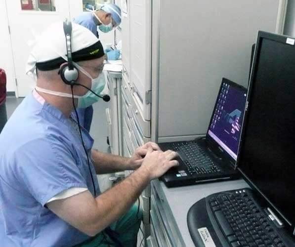 doctor sitting at computer entering information into an electronic medical record